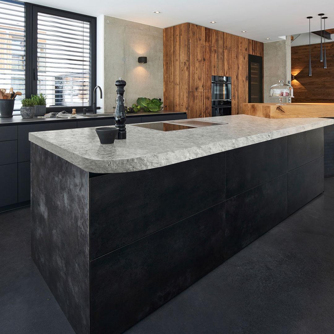 Küche mit Natursteinplatte und Kücheninsel aus Schwarzstahl