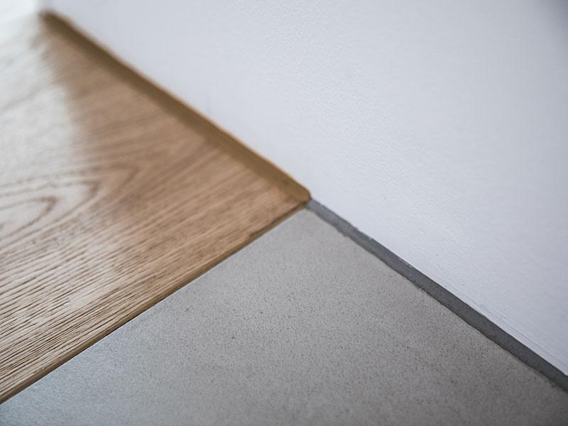 Naht zwischen Holzboden und Designboden mit Sichtestrich